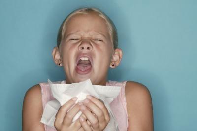 Foto di una ragazza con sintomi di allergia agli acati (starnutisce)